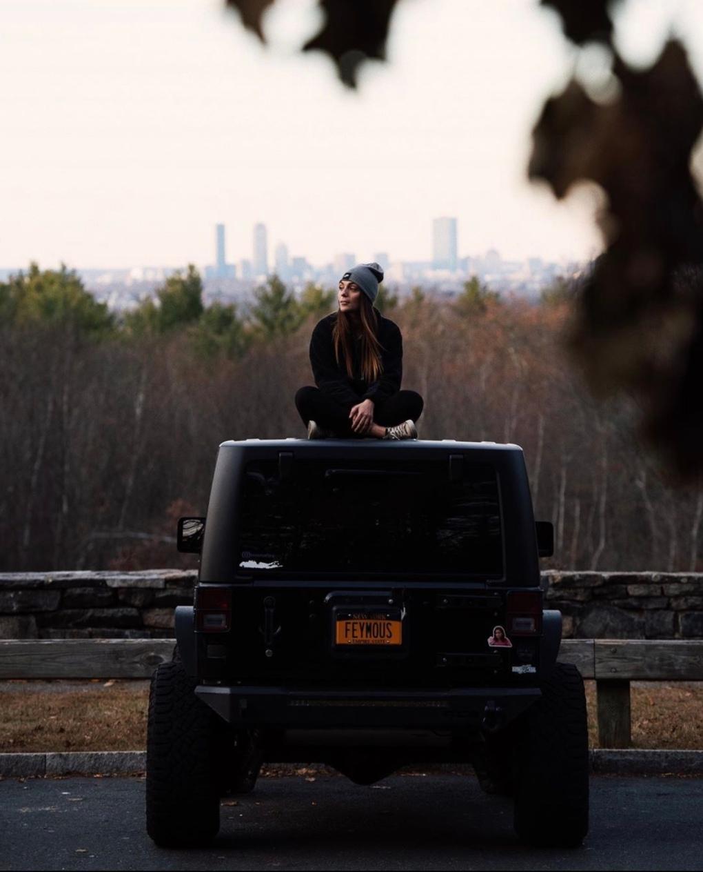 Black Jeep Wrangler in Blue Hills State Park in Massachusetts. Boston, Massachusetts is visible in the background.