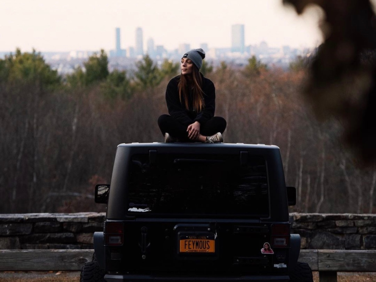 Black Jeep Wrangler in Blue Hills State Park in Massachusetts. Boston, Massachusetts is visible in the background.